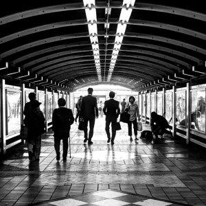 ガード下のトンネルを歩く通行人