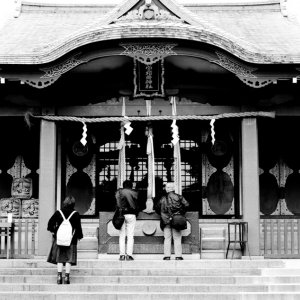 Three worshiper in front of shrine