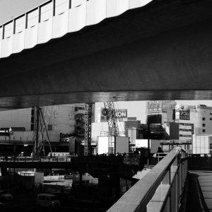歩道橋を歩く帽子の女性