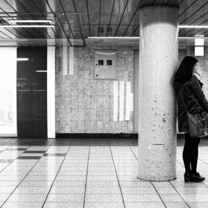 Young woman calling beside pillar