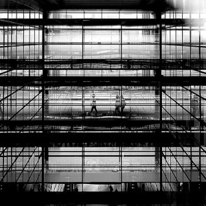 figures in the glass-walled passage