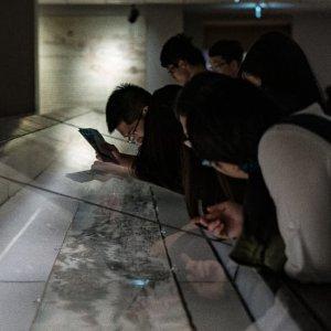 故宮博物院で巻物を見入っている人びと