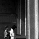 Two Women Standing Outside A Door