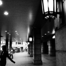 Woman Passing Between Pillars At A Quick Pace @ Tokyo