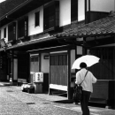 Woman With A Umbrella In Front Of Old Houses