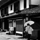 古い町並みを傘を持って歩く女性