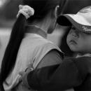 お母さんに抱えられた野球帽の男の子