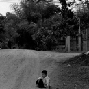 Boy Sitting On The Gravel Road