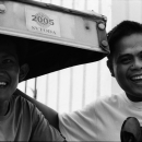 Two Cheerful Men Beside A Tricycle