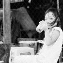 大きなグラスを片手に笑う少女
