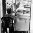 Old Woman Beside A Glass Box