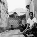 路地のバイクに腰掛けた男