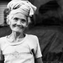 頭上にクッションを載せた年配の女性