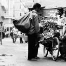 Fruit Seller And Man Carrying A Big Bag