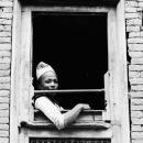 窓辺に坐るダッカ・トピの男
