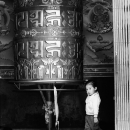 Little Girl Turing Around A Big Prayer Wheel