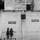 Two Girls Leaning Against The Wall