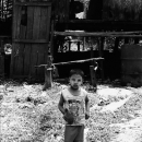 Boy Stood In Front Of A Slanted House