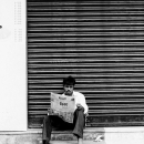 Man Reading A Newspaper In Front Of The Shutter