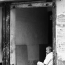 Man Sitting At The Side Of The Entrance @ India