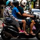 バイクに三人乗りする家族連れ