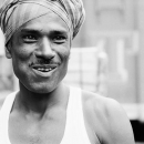 Smiling Laborer Wrapping Cloth Around His Head