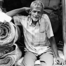 Man Sitting Beside Rolled Textiles