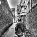 路地へと進む男