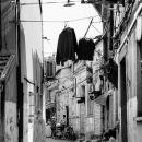 人影と洗濯物のある路地