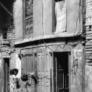 Two Girls Standing In Front Of A Wooden Door