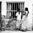 Two Women And A Bicycle In Front Of A Window @ India