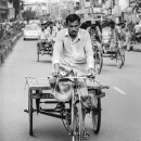 Man Pedaling The Tricycle With A Cart