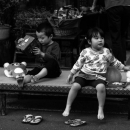 Two Kids Relaxing In Front Of A Shop