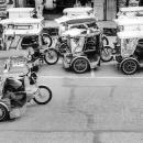Parked Trishaws And Running Trishaw