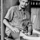 Man Relaxing Beside A Sewing Machine