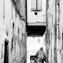 Woman Walking Between Buildings