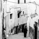 家の入る女性と路地に立つ男