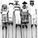 Boys Wearing Hat And Tall Stilts