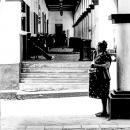Chubby Woman Standing Beside A Pillar