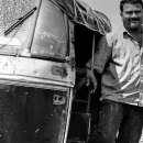 Moon-faced Man Beside An Auto Rickshaw
