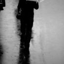 濡れた路面に傘を持つ男