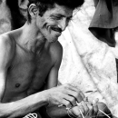 Smiling Man Repairing The Fishnet