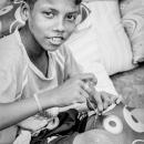 縫う男の子と山積みになったクッション