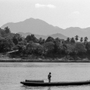 Man Standing On The Long And Thin Boat