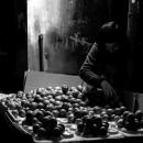 暗がりで果物を売る男
