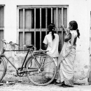 Two Women And A Bicycle In Front Of A Window