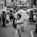 Smiling Woman Putting An Umbrella Up