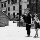 Little Boy And Little Girl In The Courtyard