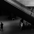Coal-black Figure Under Escalator