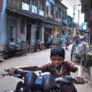 Boy Walking A Motorbike